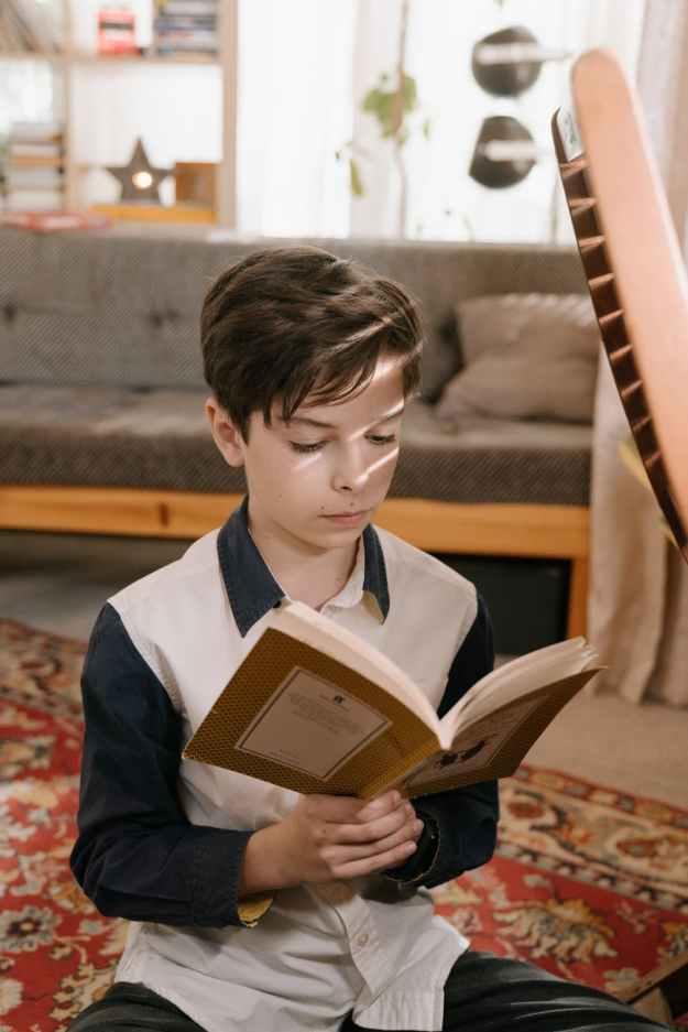 boy in white and black school uniform reading book